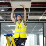 electrician fitting a sensor in office refurb